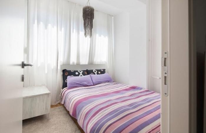 Habitación con cama grande tonos rosados y morados