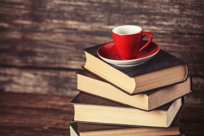 Varios libros con taza de café para leer y regalar en San Valentín
